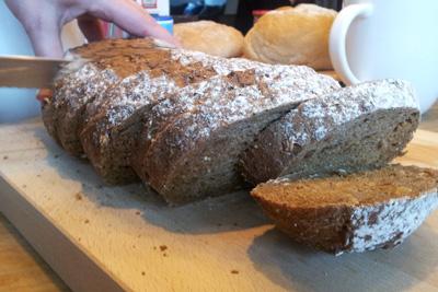 Donkerbruin brood dat gesneden wordt.