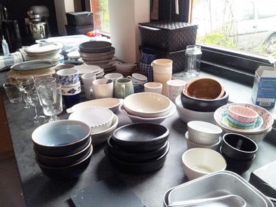 Aanrecht vol met schaaltjes, kommen, bekers en borden voor de workshop foodstyling