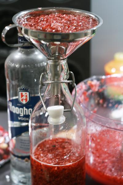 Fijngehakte cranberry's met wodka door middel van een trechter in een fles gieten.