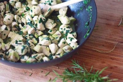 Pan met gebakken kipstukjes, champignons, spinazie en een takje rozemarijn