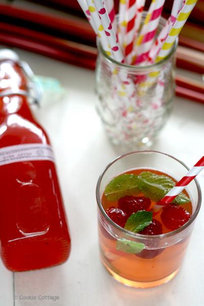 Limonade van rabarber-aardbeiensiroop met frambozen en munt