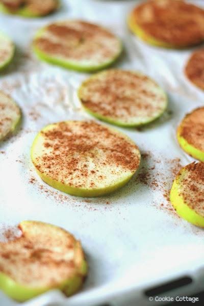 Gedroogde appelschijfjes met kaneel op een bakblik