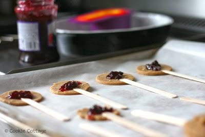 Bakblik vol koekjesrondjes met een lolliestokje en een beetje jam