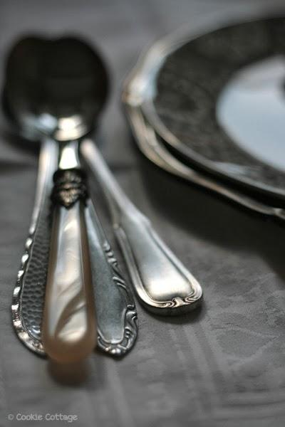 Links vier gedecoreerde sierlijke lepels, rechts twee op elkaar gestapelde borden