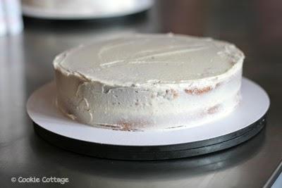Taart besmeerd met botercrème voordat de fondant erop gaat